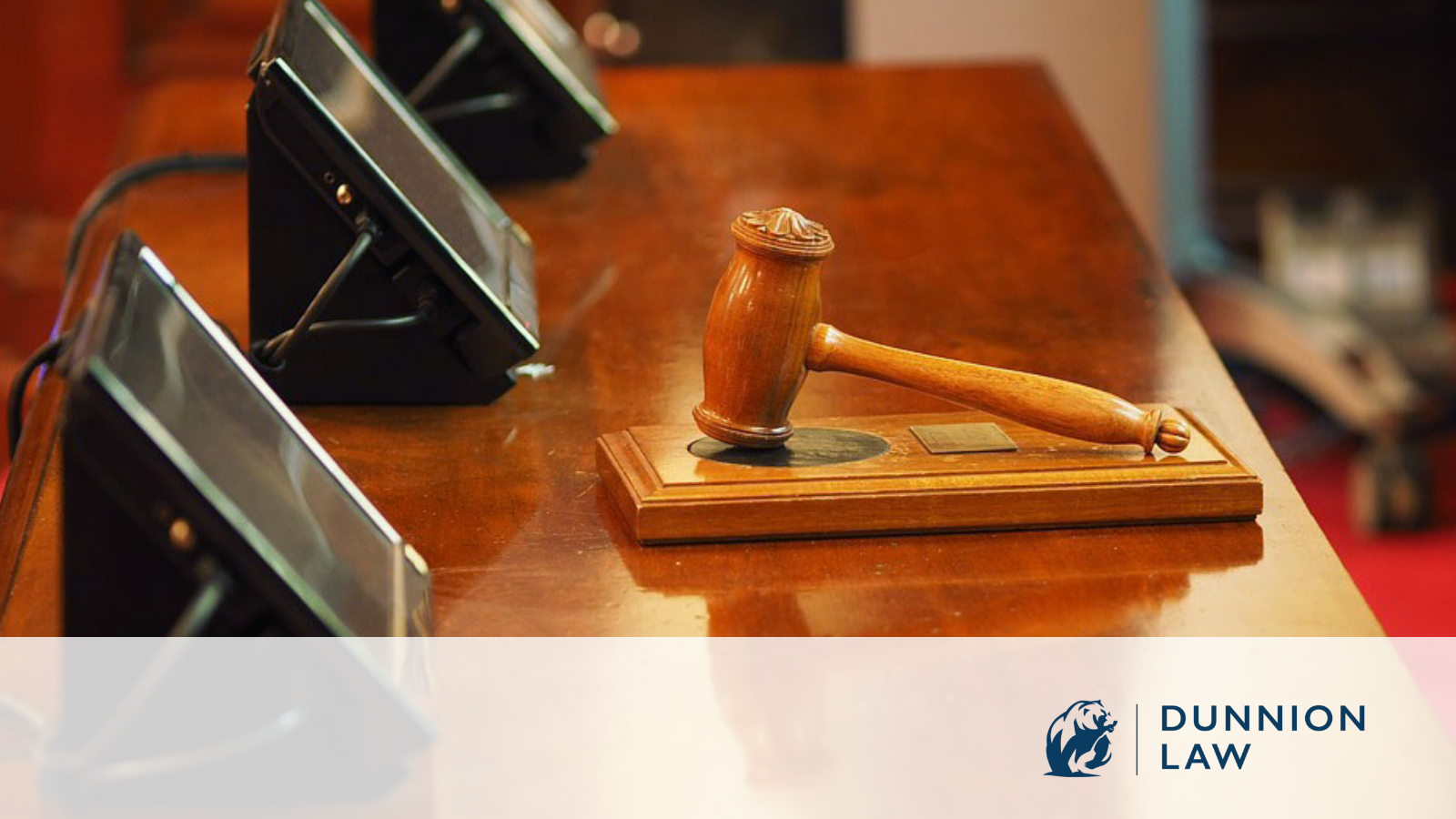 Stock photo of a gavel laying on a table in a courtroom.