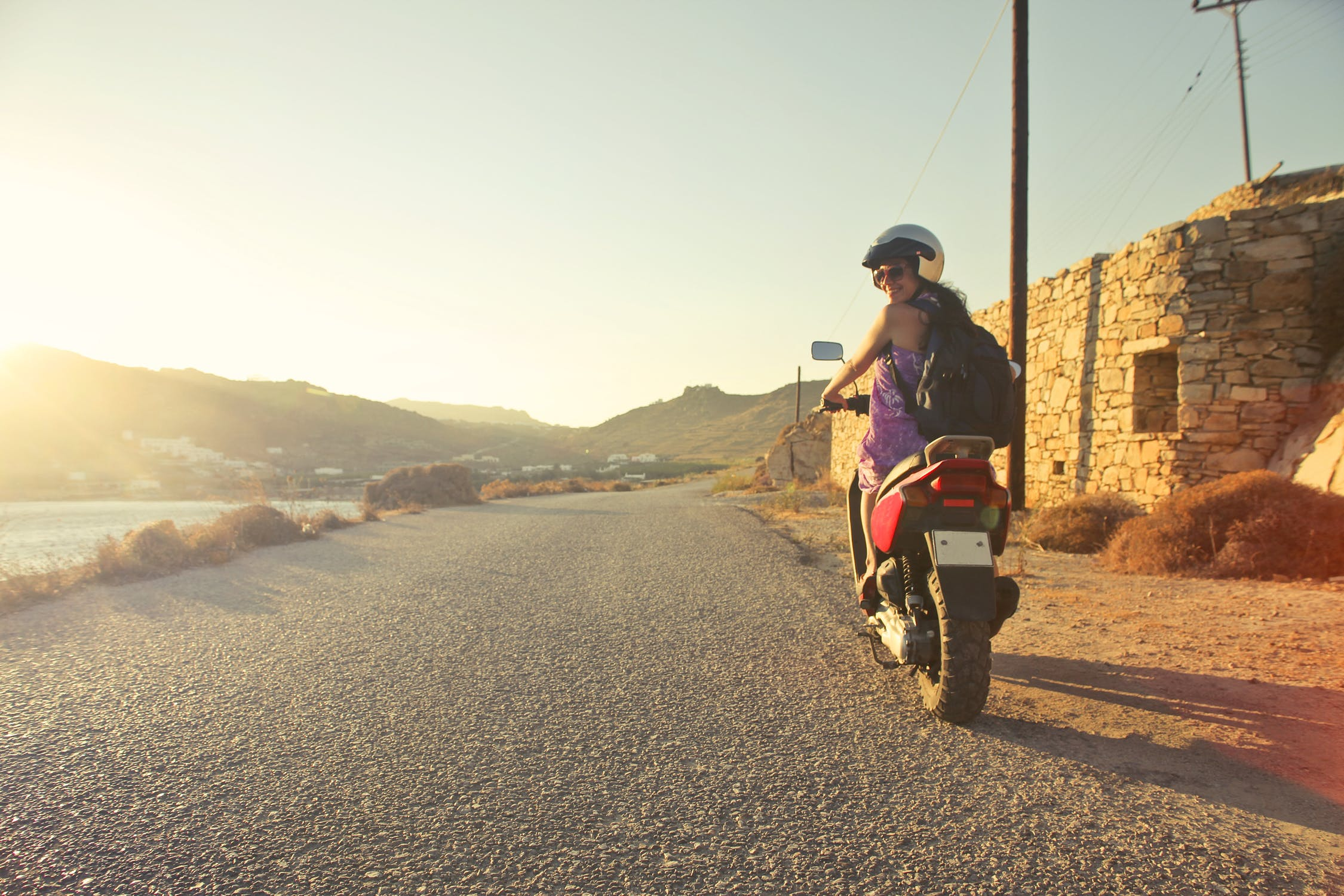 Female motorcyclist driving in the sun.