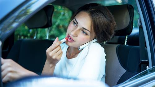 Young Woman Talking On Smart Phone While Driving Stock Photo