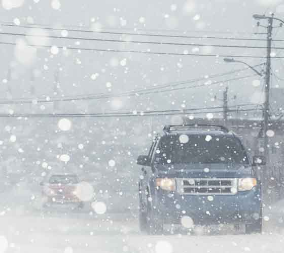 Cars Driving During A Snowstorm Stock Photo